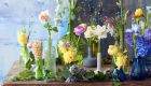 Assorted spring flowers displayed in glass and ceramic jars